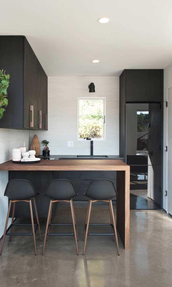 Para fechar o vão entre a geladeira preta e o teto, a solução é um armário
