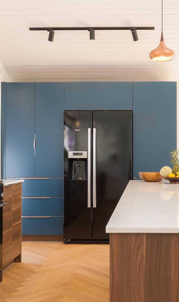 Já aqui, os armários azuis garantem o destaque da geladeira preta