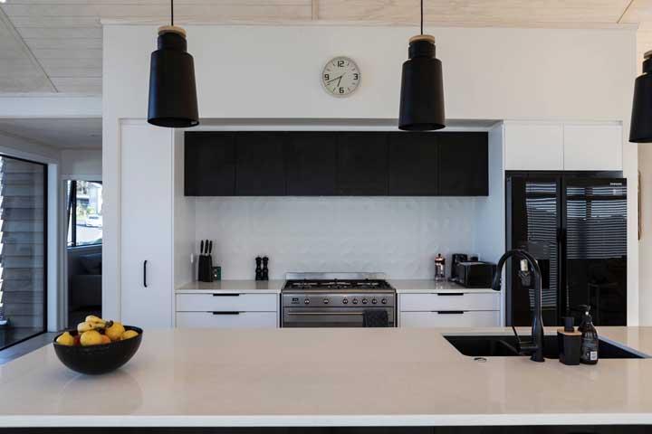 Complete o uso da geladeira preta inserindo elementos menores na mesma cor, como luminárias, fruteira e a torneira