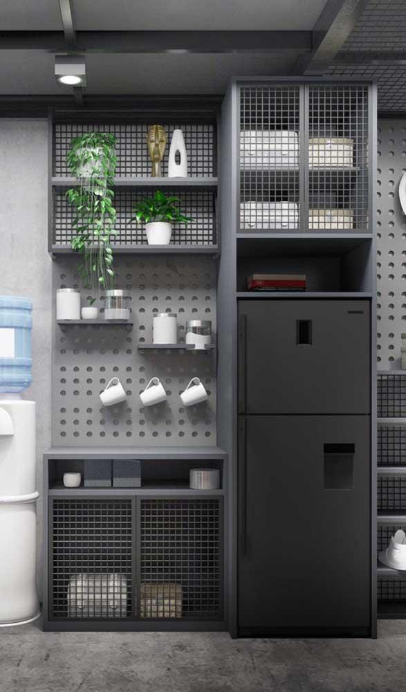 Geladeira preta frost free em meios aos armários aramados e o pegboard