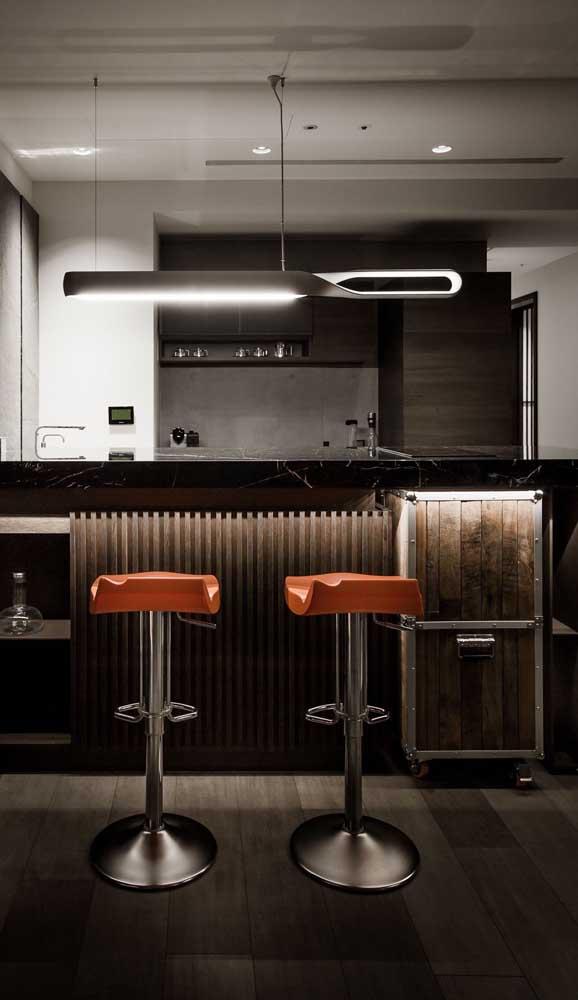 Home bar instalado na bancada da cozinha. Destaque para as banquetas que deixam o espaço mais confortável e para a iluminação difusa
