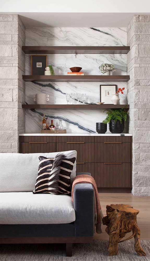Nesse outro modelo de home bar, a parede de mármore criou um lindo efeito com a parede de pedra