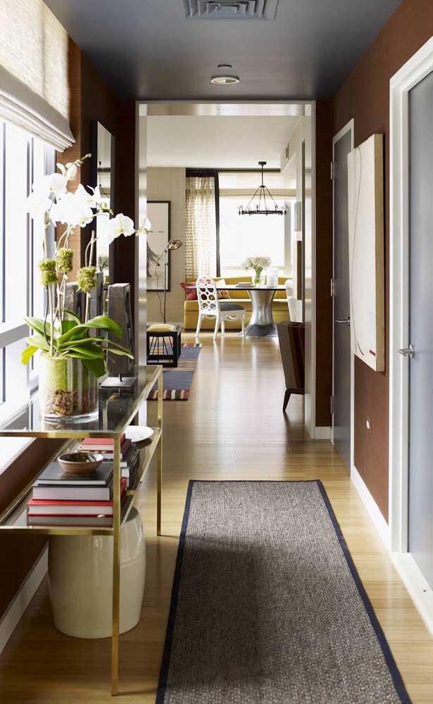 Livros e flores para decorar a bancada de vidro no corredor