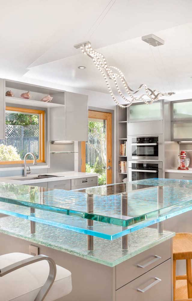 Ilha de cozinha com bancada de vidro. Repare que o cooktop foi instalado normalmente no local