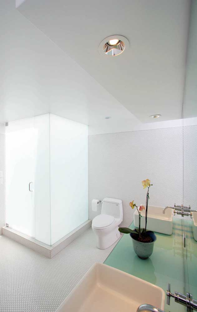 No banheiro, a bancada de vidro serve de apoio para as cubas sobrepostas