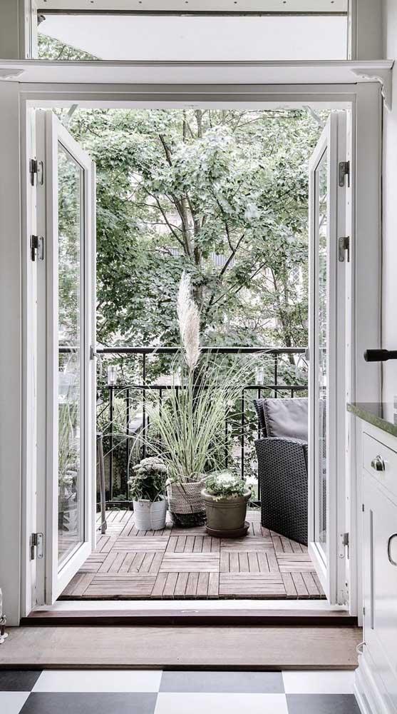 Porta francesa branca garantindo o acesso da cozinha para a varanda