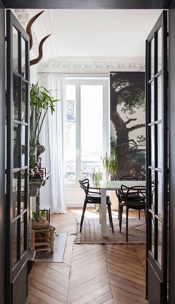 Já aqui, o modelo tradicional de porta francesa, feita em madeira com vidro quadriculado, isola a sala de estar dos demais ambientes