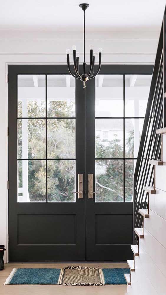 A imponente porta francesa de madeira dá as boas vindas a quem chega nessa casa
