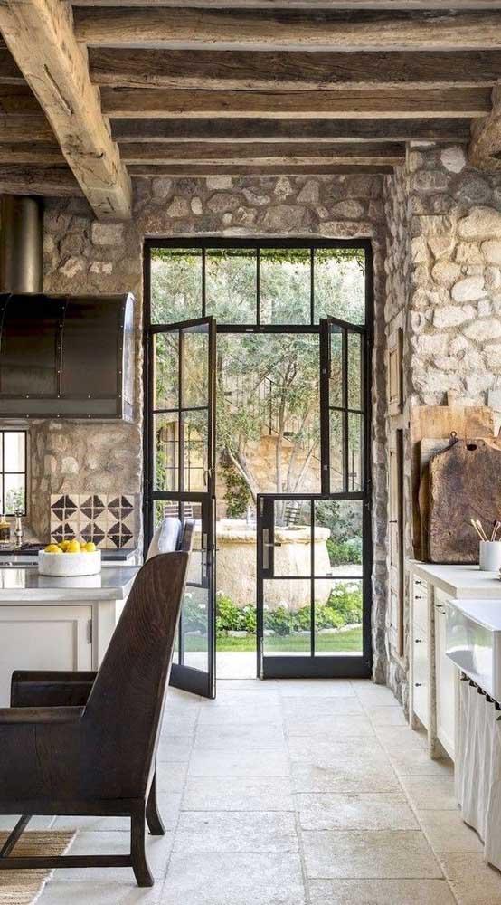 A casa de estilo rústico apostou no uso da porta francesa de ferro com abertura central