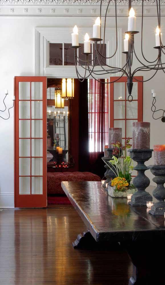 O ambiente contemporâneo apostou no uso de uma porta francesa vermelha entre a sala de jantar e a sala de estar.