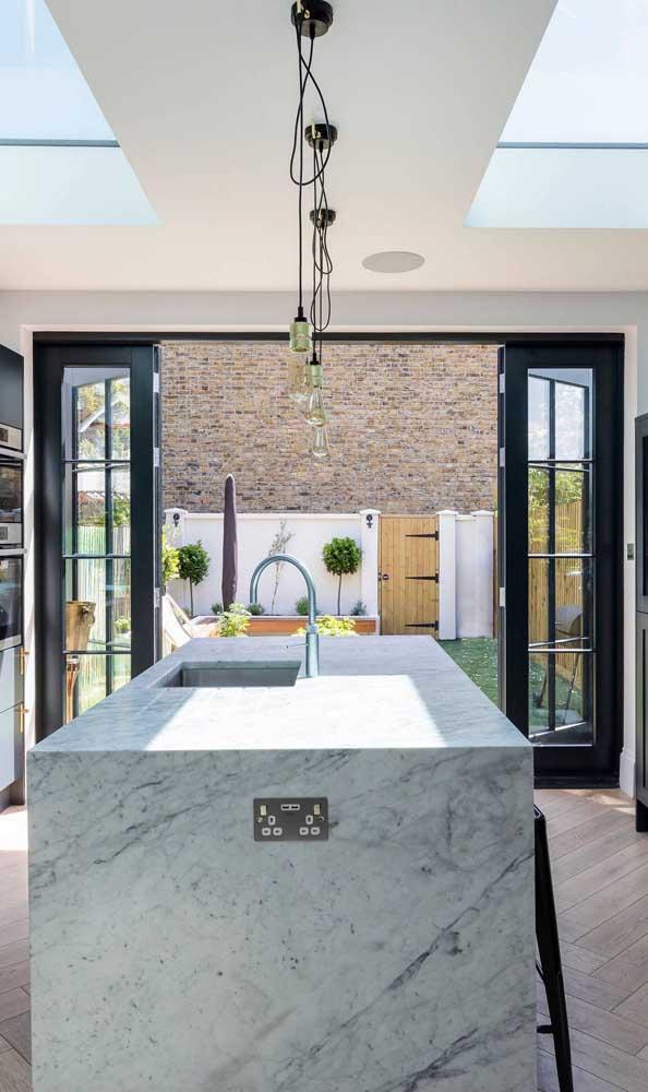 A luz do sol invade a cozinha através da porta francesa