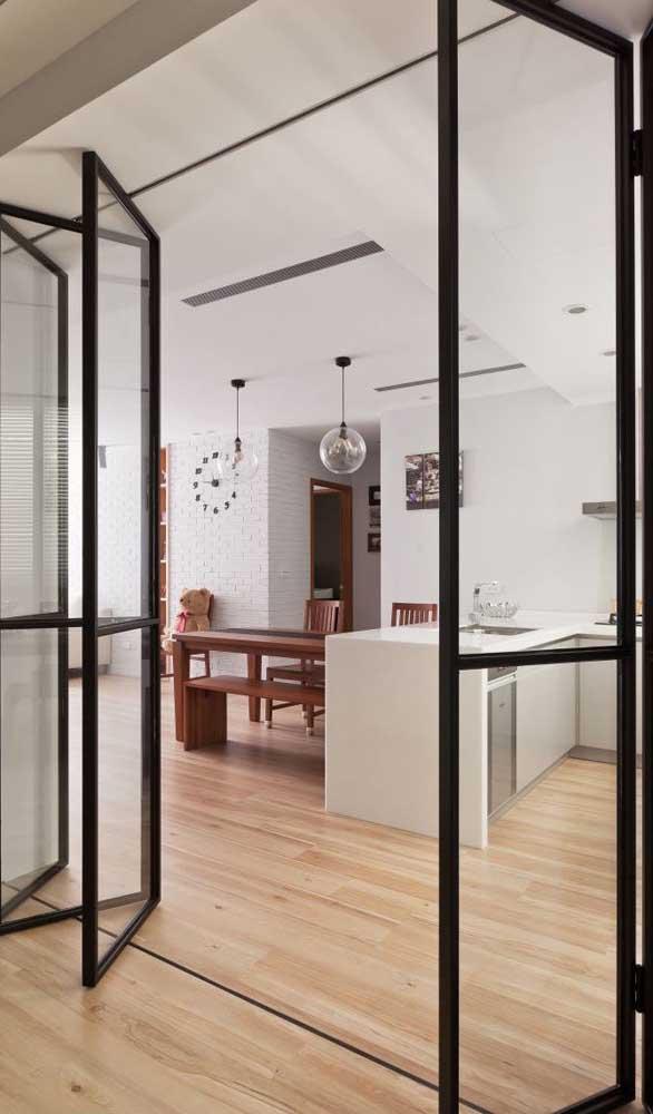 Porta francesa de ferro com três folhas de cada lado delimitando os espaços internos da casa