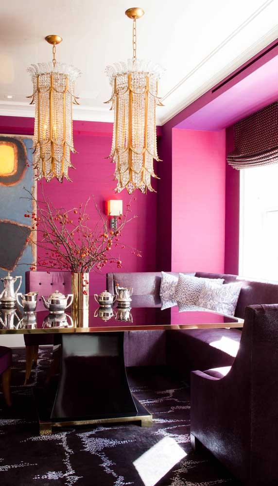 Uma sala de jantar para tirar qualquer um da monotonia! Paredes magenta combinadas ao jogo de mesa e cadeiras roxas. E, para finalizar, detalhes em dourado