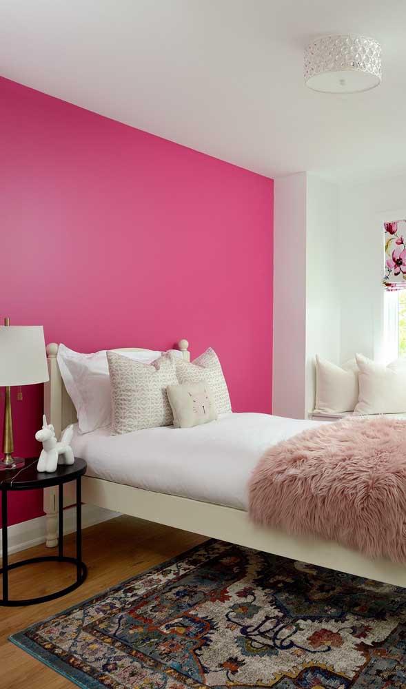 O quarto do casal não precisou de muito, bastou pintar a parede de magenta