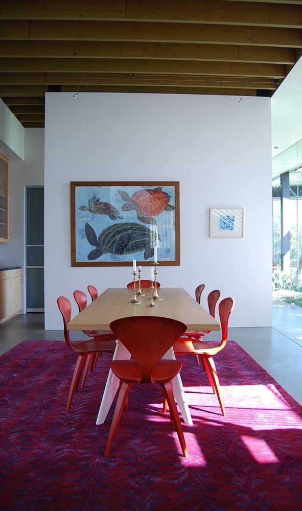 Um tapete magenta incrível para ser o destaque dessa sala de jantar. As cadeiras vermelhas fecham a proposta contemporânea de decoração