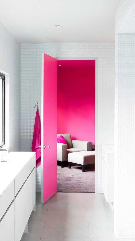 O banheiro branco dá acesso ao quarto todo decorado com a cor magenta