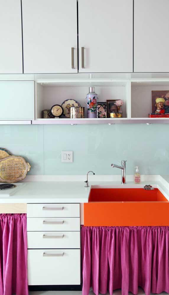 Essa cozinha de móveis brancos ganhou vida com a cortininha de pia magenta e a cuba laranja