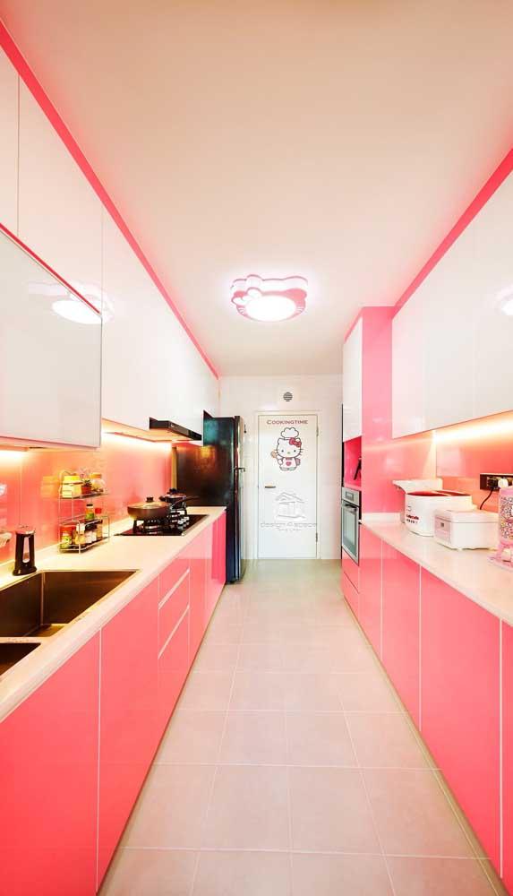 Cozinha corredor decorada em tons de branco e magenta. Destaque para a iluminação embutida nos armários