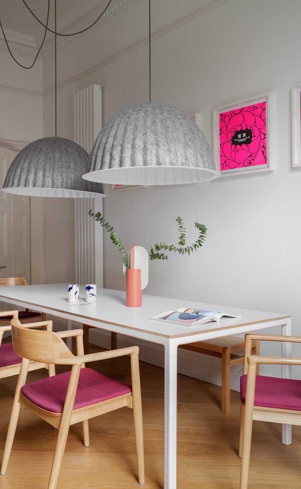 Nessa sala de jantar, o magenta ganhou espaço no estofado das cadeiras e no pequeno quadro na parede, mas repare que a cor vem em tons diferentes
