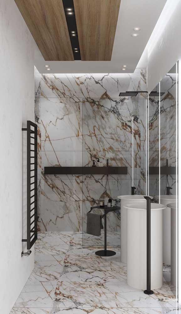 Banheiro moderno com luminária tipo spot embutida no teto rebaixado. Luzes de LED no espelho completam a proposta de iluminação