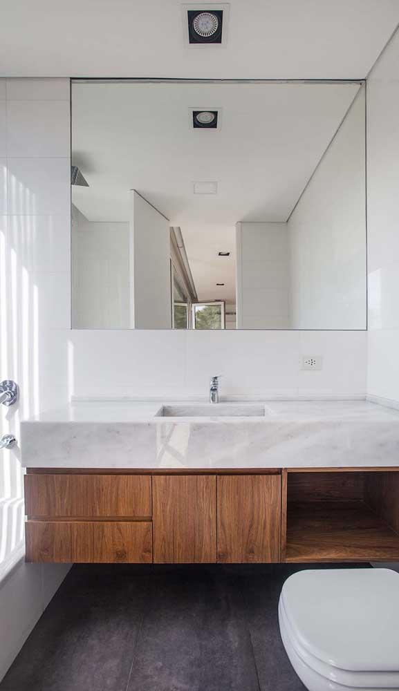 Luminária pendente sobre o espelho e spots embutidos no teto: conjunto para deixar o banheiro funcional e muito acolhedor