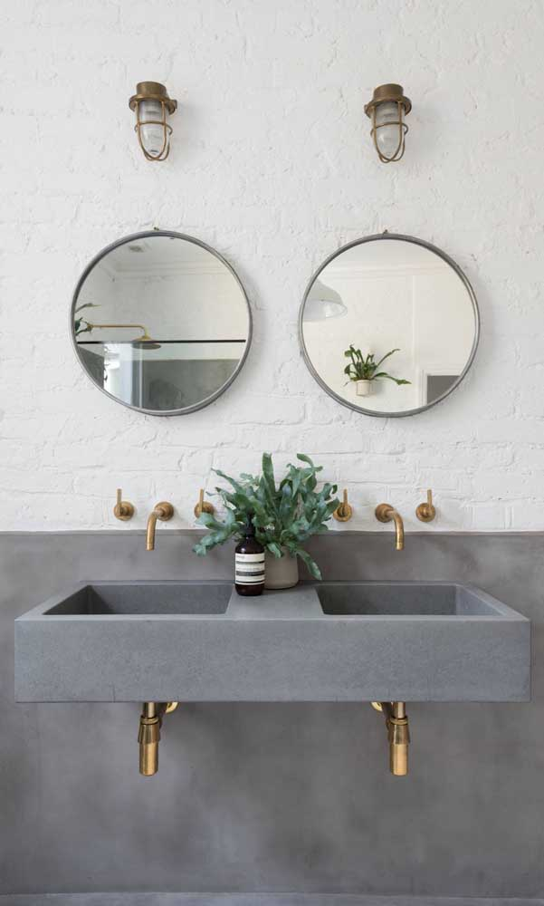 Banheiro de casal com luminárias de parede sobre cada espelho