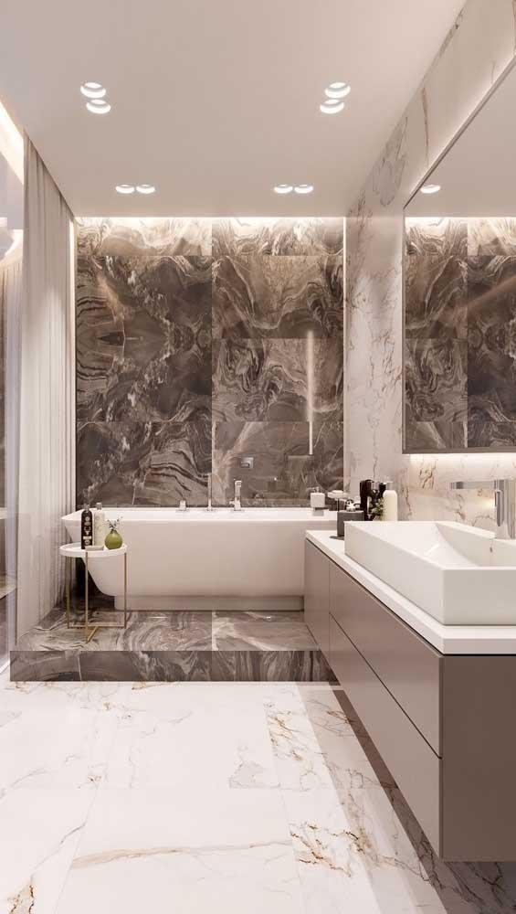 As luminárias também ajudam a destacar pontos da decoração do banheiro, como é o caso aqui, onde as luzes valorizam o mármore
