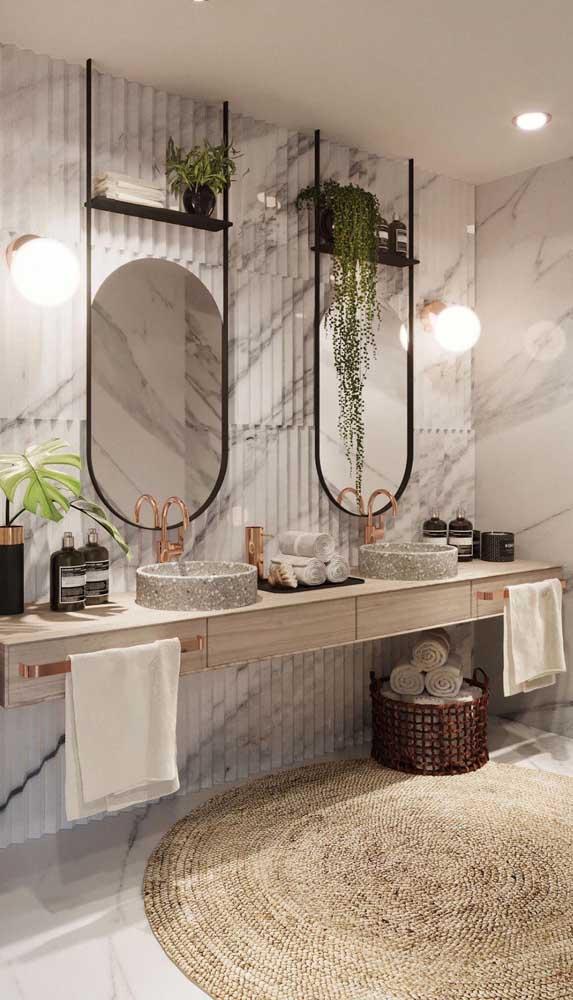 Banheiro de casal com luminárias de parede ao lado do espelho