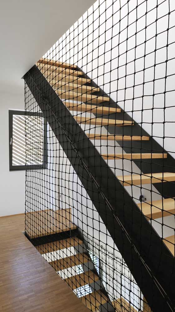 Rede de proteção para a escada. A cor preta ajuda a valorizar a decoração