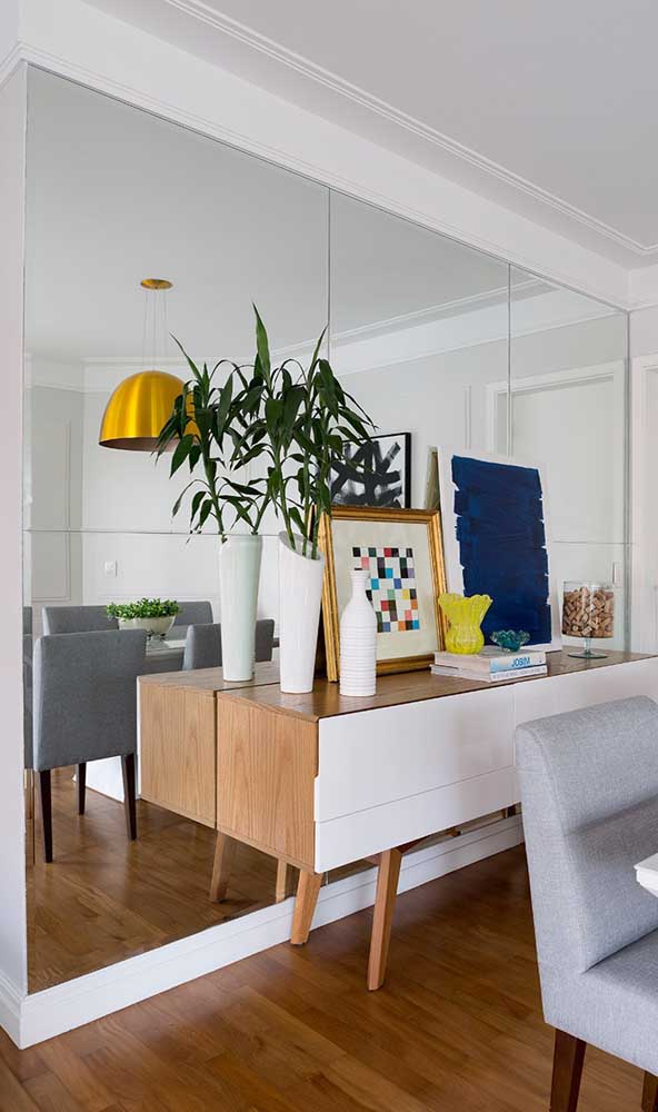 Essa sala de jantar ganhou uma parede inteirinha revestida com espelho bisotado, ampliando visualmente o ambiente