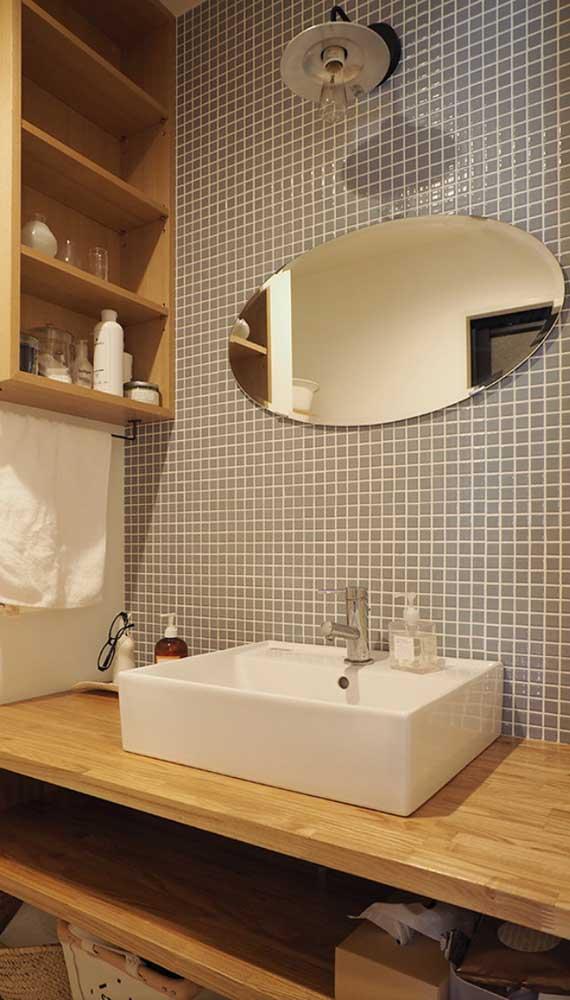 Espelho bisotado em formato oval sobre a bancada do banheiro