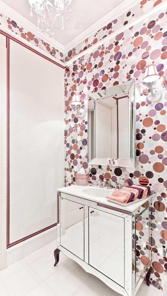Já esse outro banheiro cheio de cor se destaca pelo espelho bisotado na parede e no revestimento do armarinho