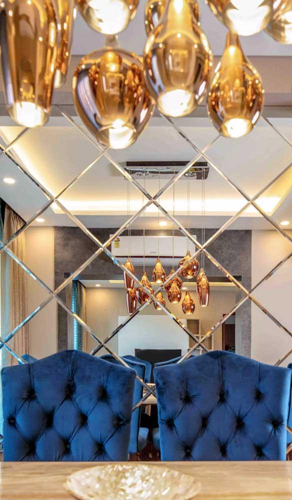 A sala de jantar elegante e contemporânea apostou em um mosaico de espelho bisotado para se diferenciar