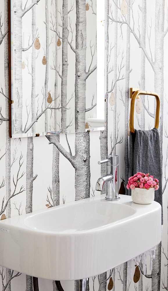 Nesse outro banheiro, o espelho bisotado ganhou o papel de um grande ilusor de ótica ao refletir a imagem do papel de parede a frente