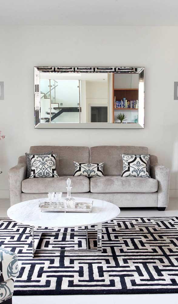Espelho bisotado na parede e nos pés da mesinha de centro dessa sala