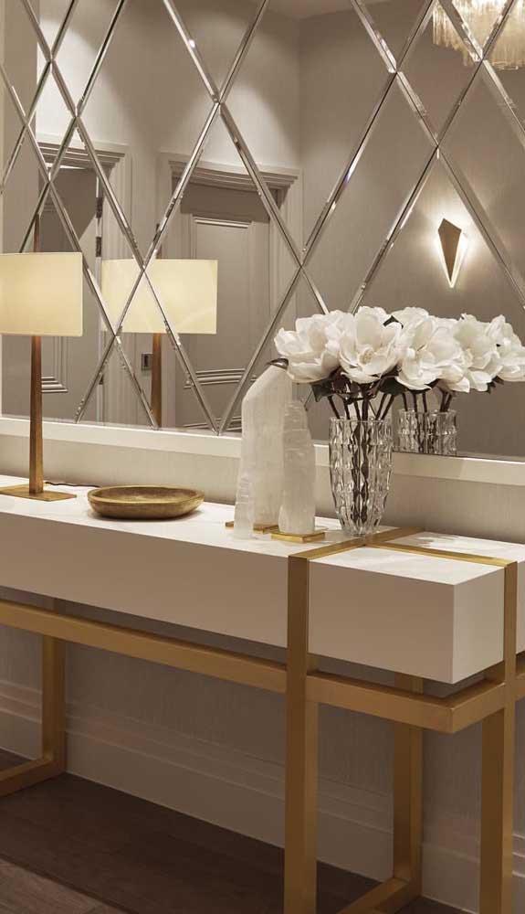 Os objetos em dourado conferem um toque extra de elegância ao painel de espelho bisotado