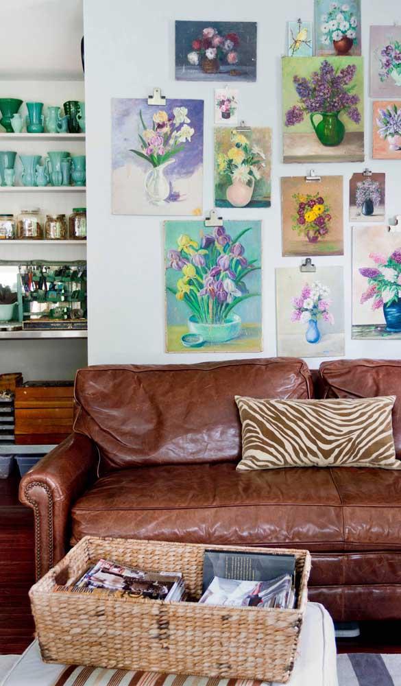 Aqui, o sofá retrô de couro se destaca novamente e se completa com a parede repleta de pinturas