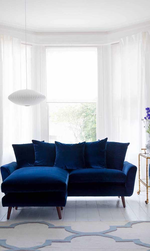 Essa sala clean, toda branca, apostou sem medo de ser feliz em um belíssimo sofá retrô de veludo azul