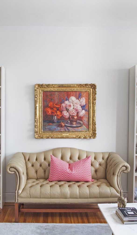 Elementos pontuais valorizam a estética retrô do sofá, como é o caso do quadro com moldura clássica