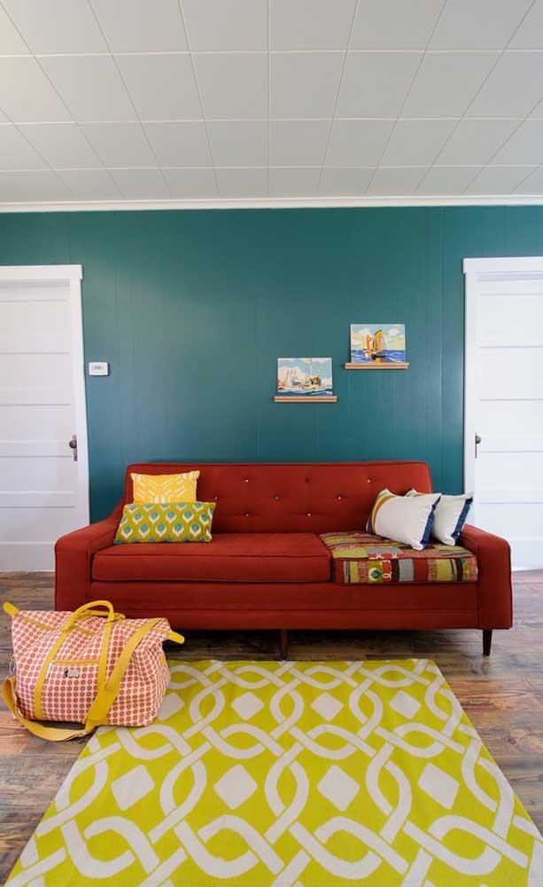 As cores complementares invadiram essa sala de estar, passando pelo sofá retrô vermelho, a parede azul e o tapete amarelo