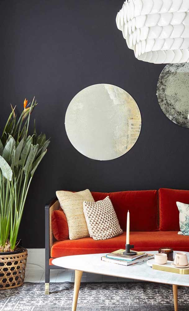 A parede preta garantiu todo o destaque para o sofá retrô vermelho de veludo