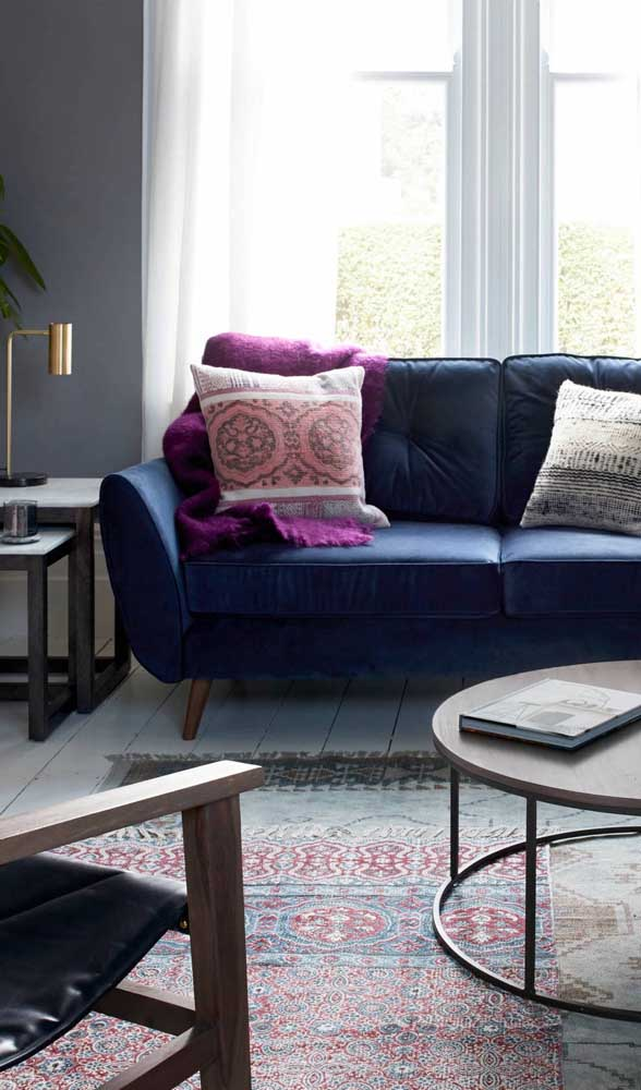 Aposte em mantas e almofadas de cores contrastantes para decorar o seu sofá retrô