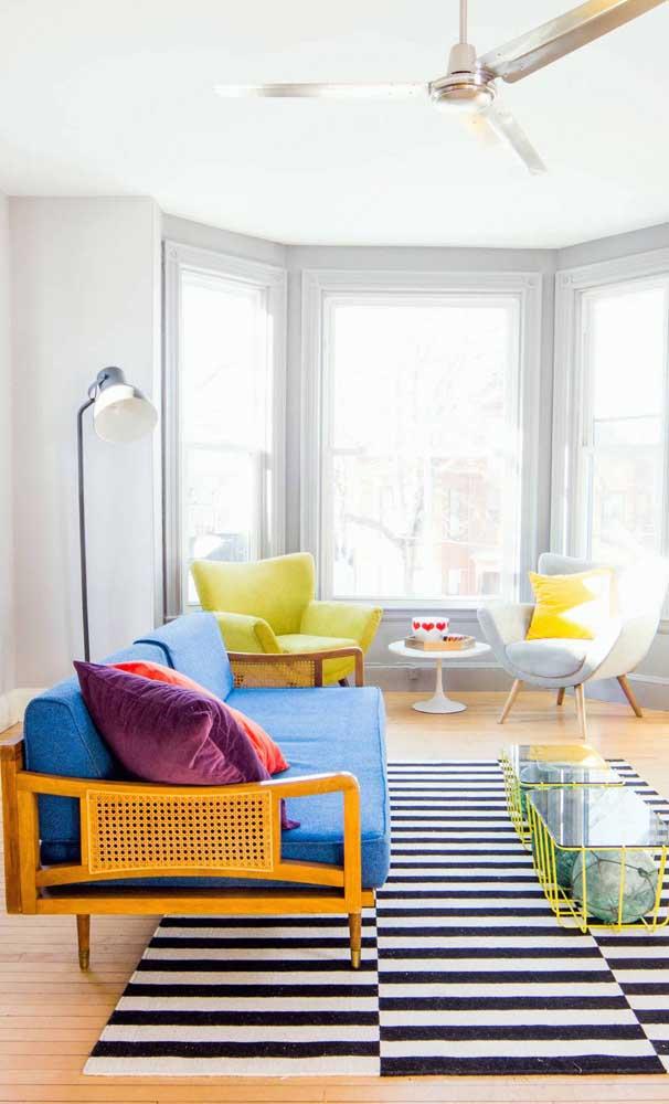 Linda composição entre o sofá retrô e o tapete de listras preto e branco