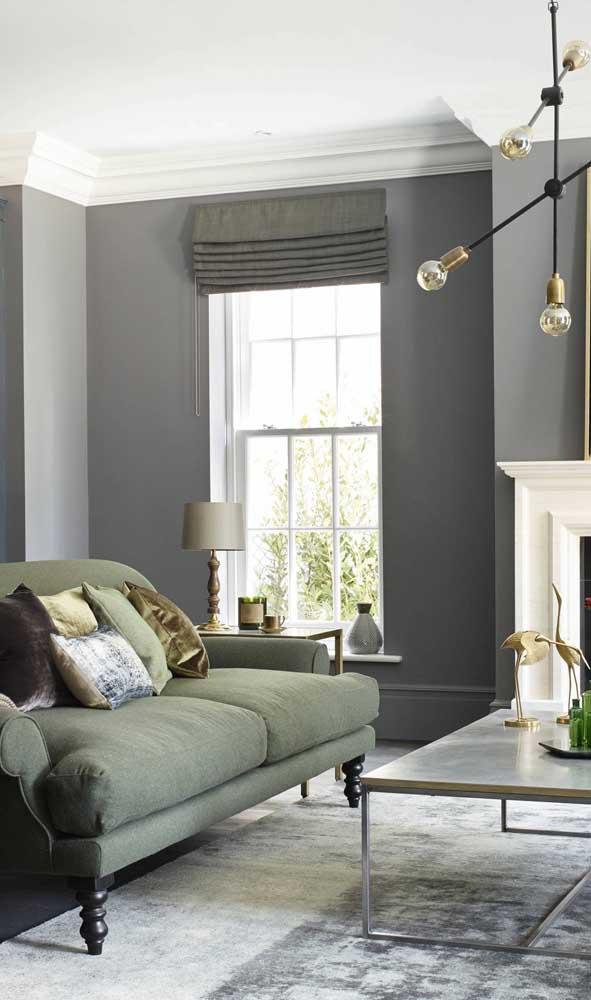 Para acompanhar os tons sóbrios da decor foi escolhido um sofá retrô verde