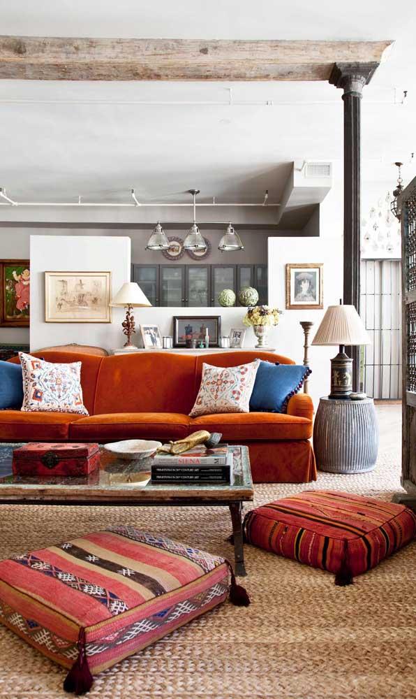 Essa sala de elementos clássicos e rústicos se destaca com a presença do sofá retrô vermelho de veludo