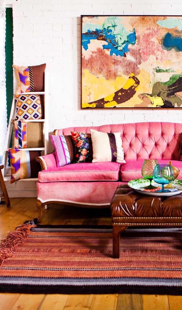 Belíssimo contra ponto entre o sofá retrô pink e a parede de tijolinhos