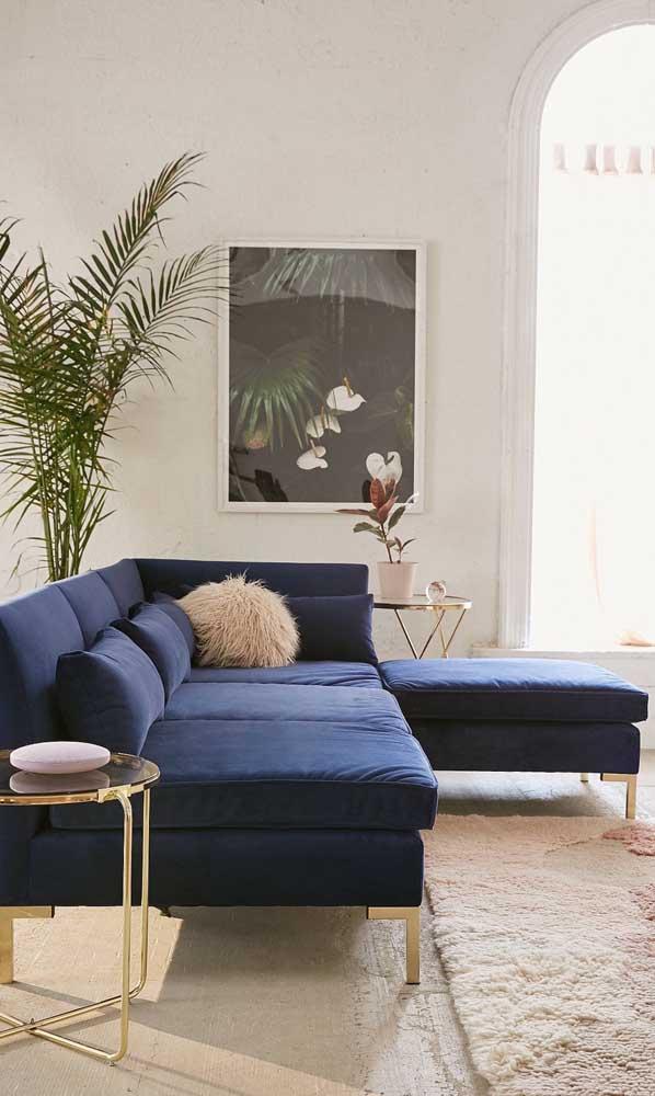 Mix entre o retrô e o moderno nesse sofá azul com detalhes dourados