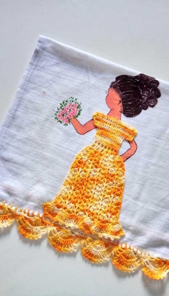 A menina pintada à mão no pano de prato ganhou um charmoso vestido de crochê que se estende até formar o barrado
