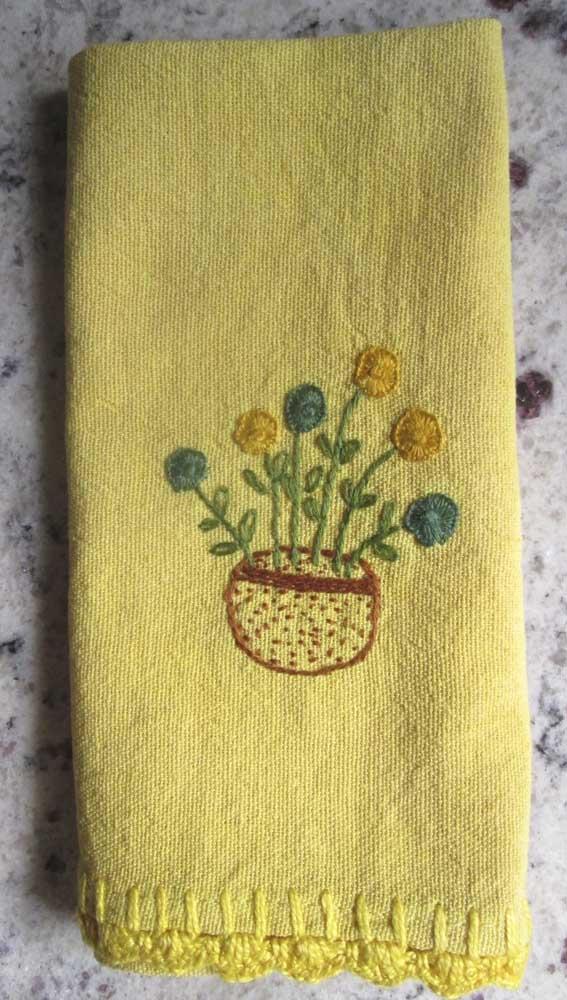 Já aqui, o vasinho simples bordado no pano de prato ganhou a companhia do barradinho simples de crochê