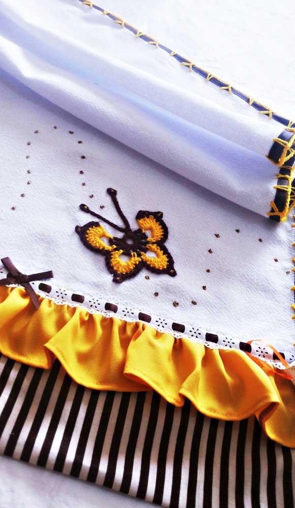 Nesse outro modelo de pano de prato, o barrado de tecido e cetim ganhou a companhia de borboletas de crochê
